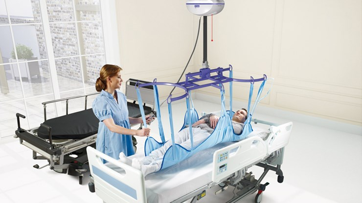 ArjoHuntleigh-patient-transfer-solutions-ceiling-lift-caregiver-with-patient-maxi-sky-2.jpg